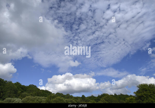 Cirrus and cumulus clouds against a blue sky - Stock Image
