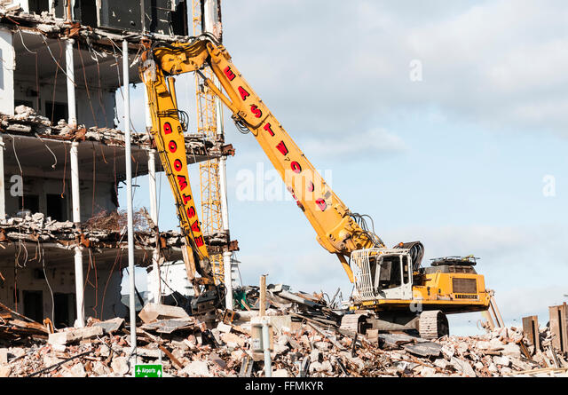 High reach excavator being used to demolish a building. - Stock Image