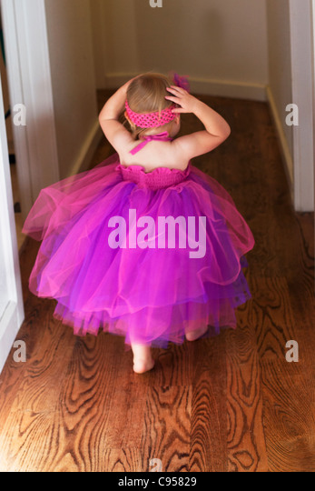 Toddler running down hallway wearing pink dress. - Stock Image