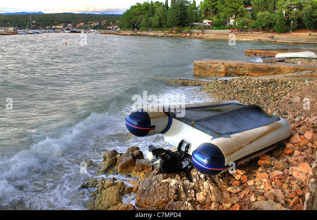 Boat crashed on the rocks sea shore after strong storm, Malinska, croatia - Stock Image