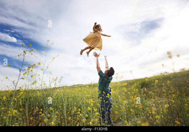 Father throwing daughter in the air - Stock Image