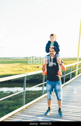 Portrait of father giving son (8-9) piggyback ride - Stock Image