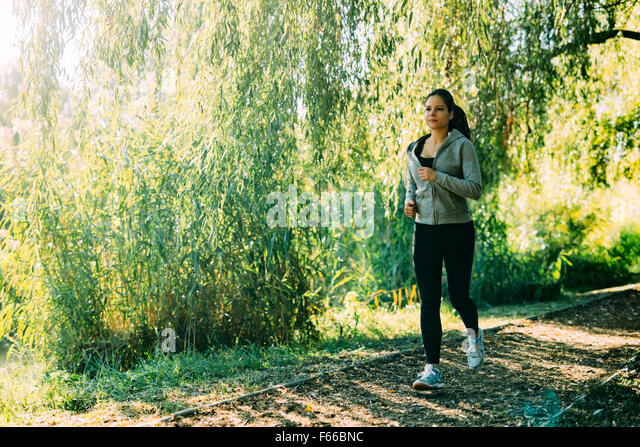 Fit woman jogging outdoors in nature - Stock Image