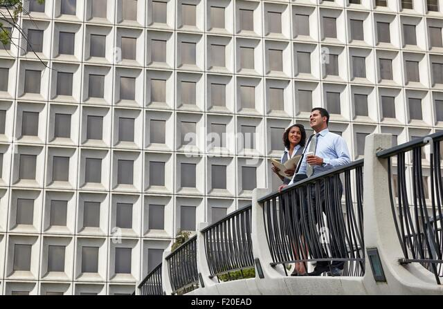 Business people standing behind railings in front of built structure - Stock-Bilder