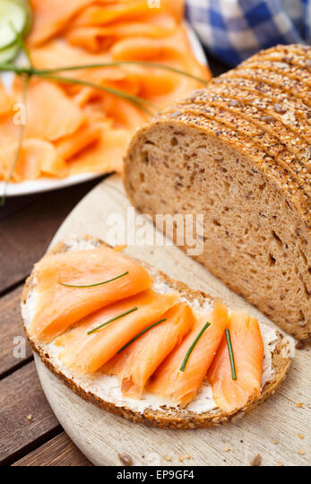 Delicious smoked salmon sandwich on a cutting board - Stock Image