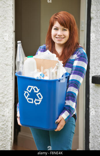 Teenage Girl Emptying Recycling At Home - Stock Image