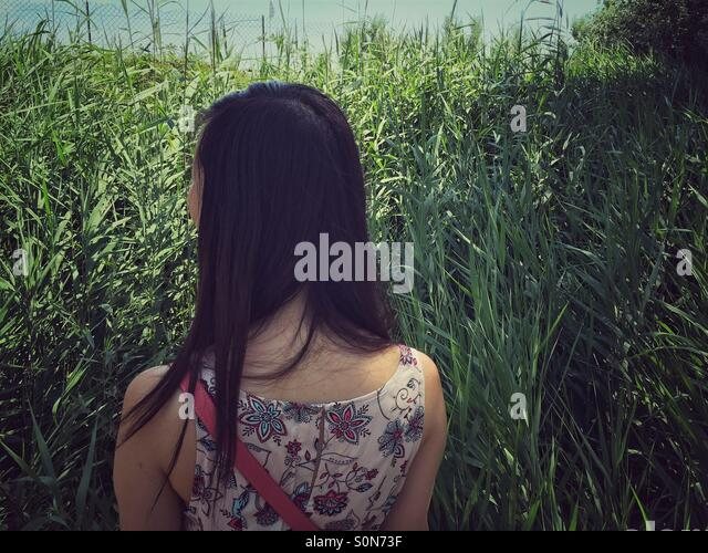 Rear view of woman walking through field, Rhone Alpes, France - Stock Image