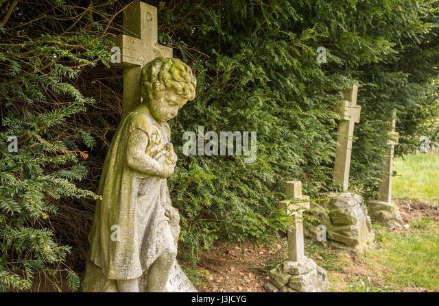 A churchyard with childrens graves under yew tree - Stock-Bilder