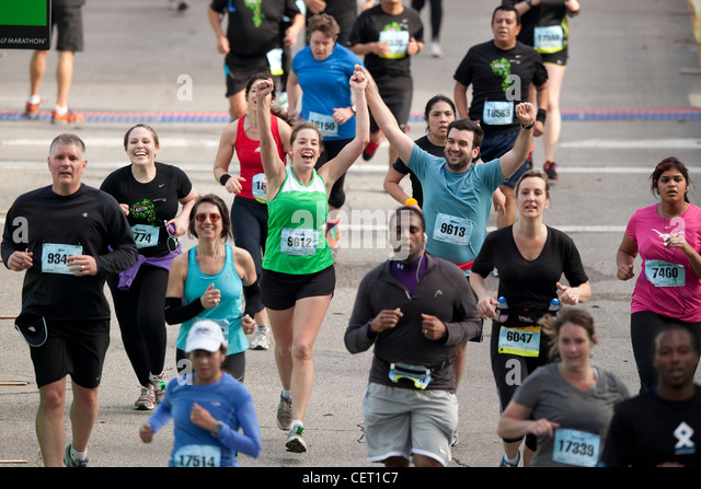 Athletes celebrate as more than 18,000 runners pounded the streets of downtown Austin for the annual marathon race - Stock Image