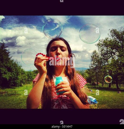 Young girl blowing bubbles on a summers day. - Stock-Bilder