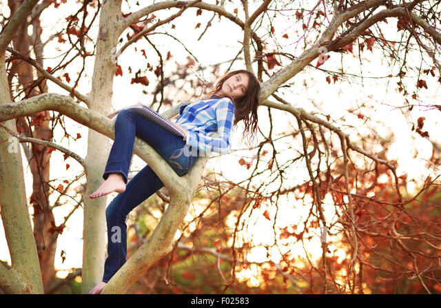 Teenage girl sitting in a tree with drawing pad - Stock-Bilder