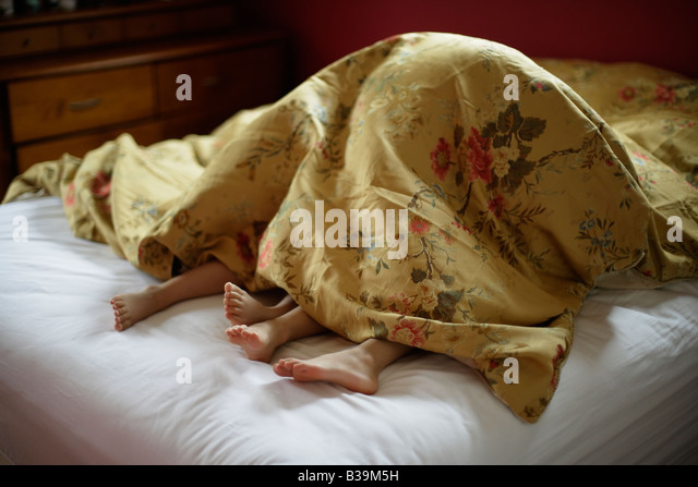 Brother and sister underneath covers of parent s bed Girl aged 5 and boy 6 - Stock-Bilder