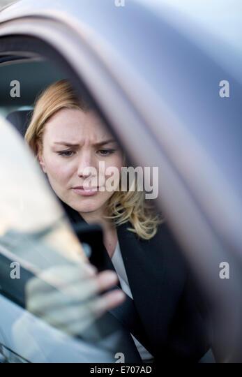 Worried businesswoman reading texts on smartphone in city traffic jam - Stock-Bilder