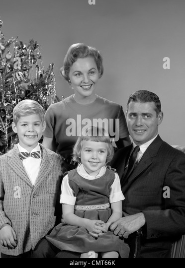 1950s 1960s FAMILY PORTRAIT SMILING FATHER MOTHER DAUGHTER SON SITTING TOGETHER IN FRONT OF INDOOR CHRISTMAS TREE - Stock Image