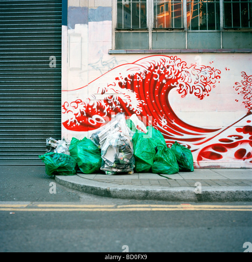 Rubbish left next to street art in the style of Japanese artist Hokusai in Shoreditch, London - Stock Image