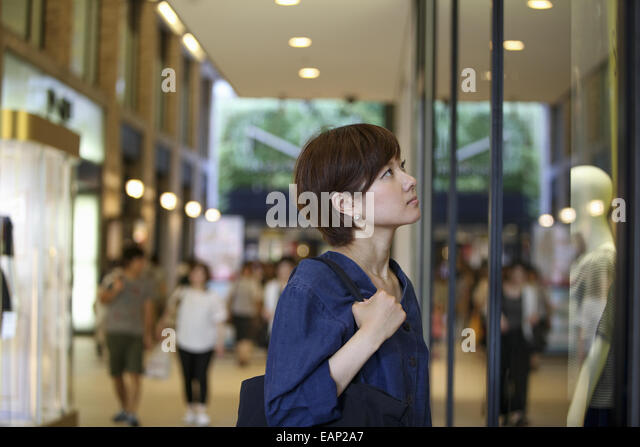 A woman in a shopping mall looking at a shop window display. - Stock Image