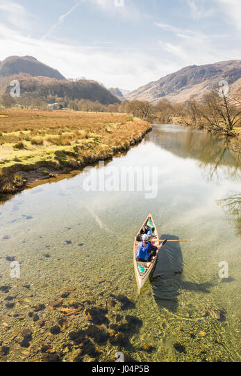 Canoeing Canoe in the Lake District, England, UK - one man and his dog conoeing on the River Derwent, Derwentwater - Stock Image