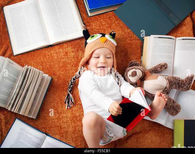 One year old baby reading books with teddy bear - Stock Image