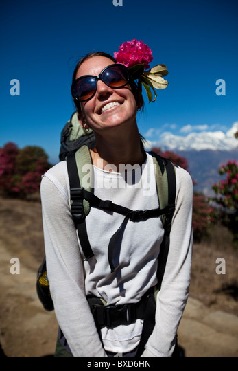 A female trekker wearing a flower in her hair stops to let the sun shine on her face. - Stock Image