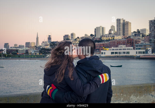 A young couple in love at Aquatic Park Pier, with the Aquatic Park Bathhouse, Ghirardelli Square and San Francisco - Stock Image