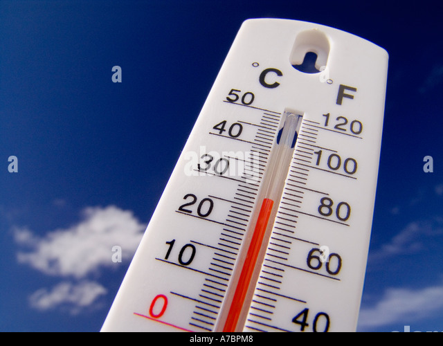 Thermometer displays a hot and sunny 28 degrees centigrade ( 82F) against a bright blue sky - Stock Image