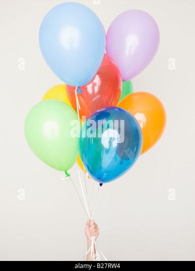 Child holding assorted balloons - Stock Image