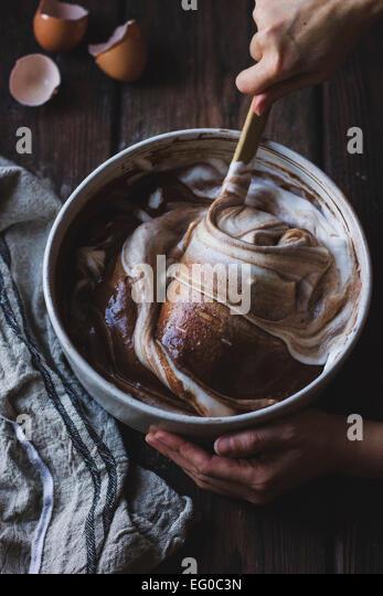 Folding egg whites into chocolate cake batter - Stock Image