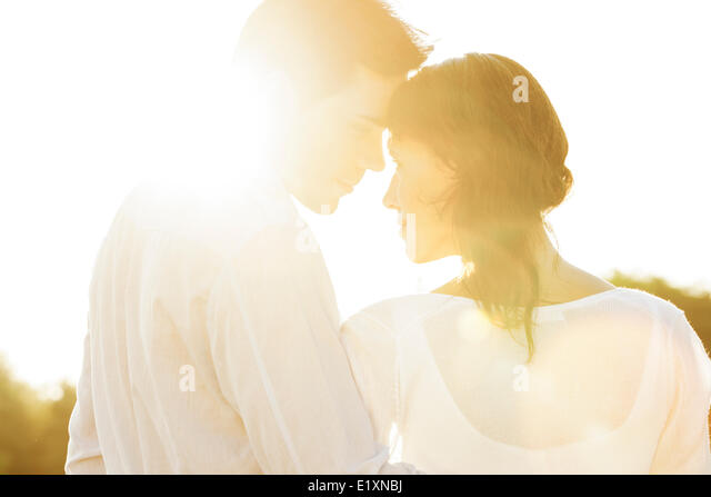Rear view of romantic couple looking at each other during summer - Stock-Bilder