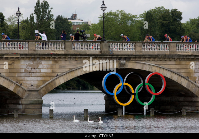Triathletes cycle over Serpentine Bridge in London's Hyde Park for the Mens' Triathlon competition during - Stock Image