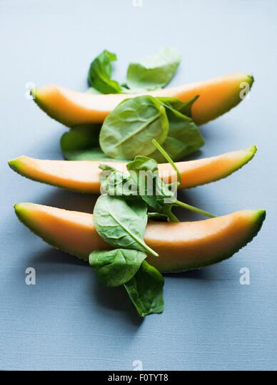 Three slices of fresh melon and spinach - Stock-Bilder