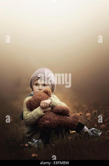 Girl cuddling teddy bear - Stock Image