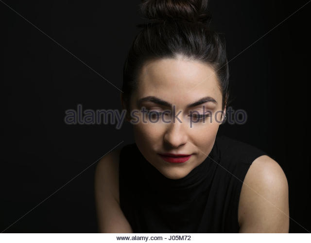 Pensive, sad brunette woman against black background - Stock Image