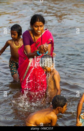 Indian woman bathing his son at Tungabhadra river, Hampi, Karnataka, India - Stock-Bilder