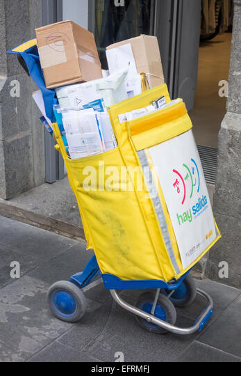 Spanish postal worker leaves trolley/bag outside shop while delivering mail. - Stock Image