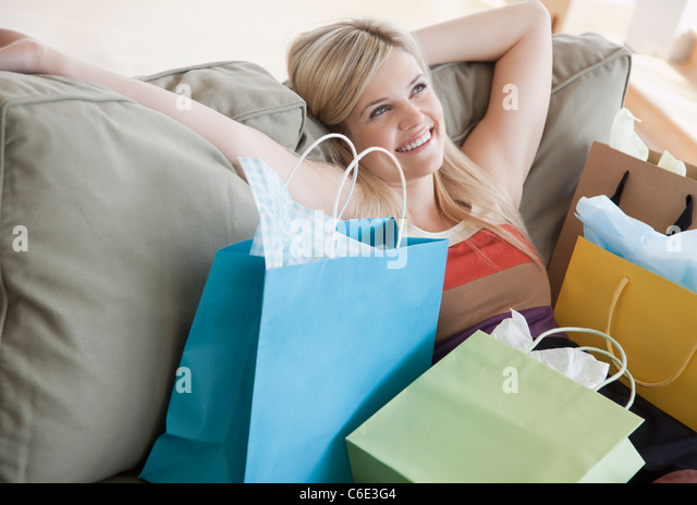 USA, New Jersey, Jersey City, Young woman sitting on sofa surrounded by shopping bags - Stock Image
