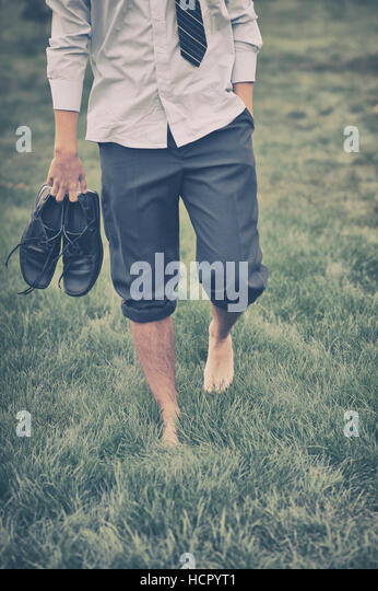 Man walks on grass - Stock Image