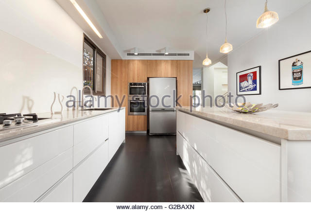 Villa in Modin by Tomer Peretz. Modern, minimalist white kitchen with stainless steel appliances. Lights hanging - Stock Image
