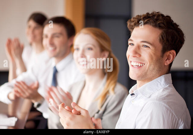 Young business professionals applauding during meeting - Stock Image