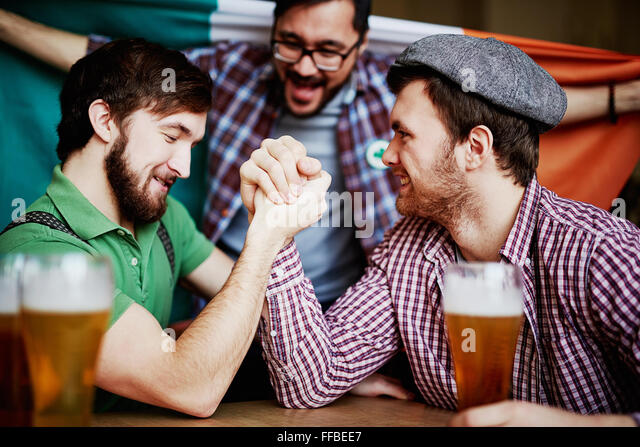 Two strong young men arm-wrestling in pub - Stock Image