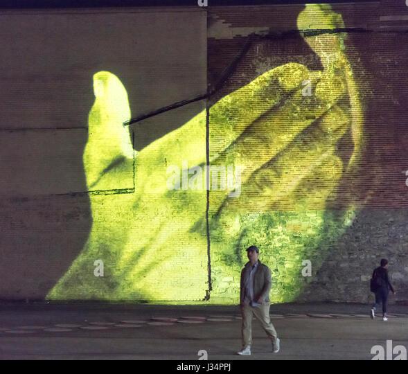 Boulevard St Laurent, Montreal, Quebec, Canada - 27 April 2017: pedestrians walk in front of video of yellow hands - Stock Image