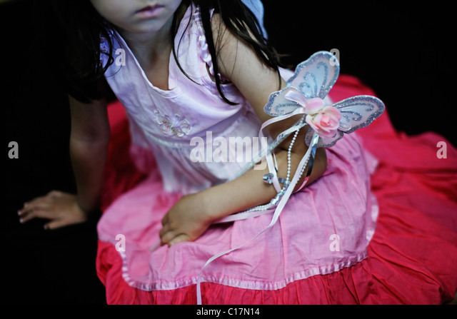 Five year old girl in pink dress with butterfly wand and fairy wings - Stock Image