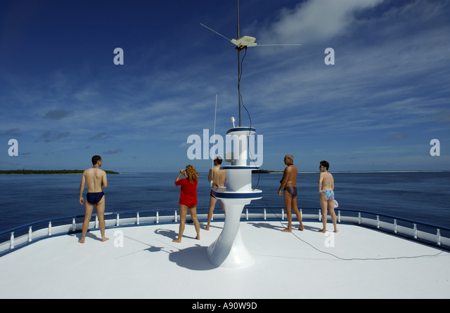 People looking out to sea from the upper deck of a diver's cruise boat, Maldives. - Stock Image