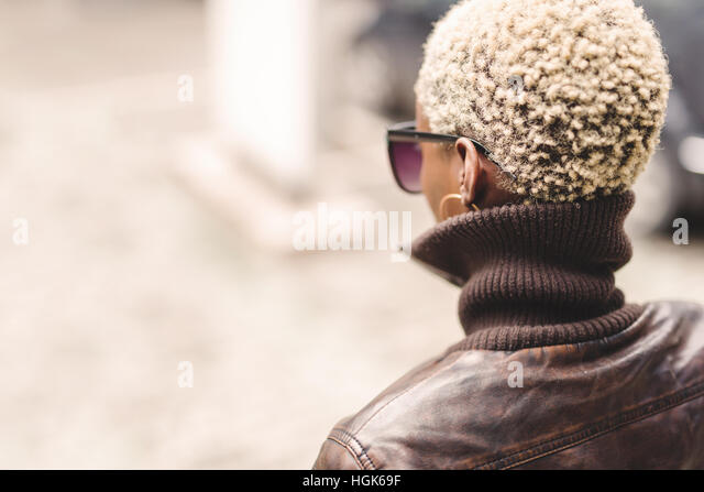 Black woman with short blond afro hair wearing glasses - Stock Image