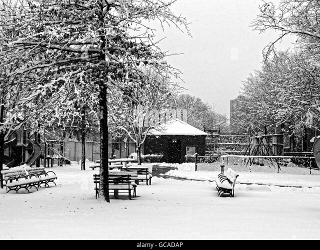 Serene park and benches during a Winter snowfall. - Stock Image