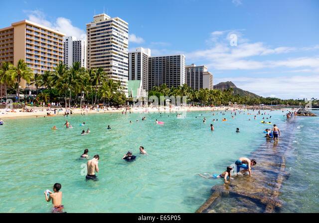 Hawaii Hawaiian Honolulu Waikiki Beach resort Kuhio Beach State Park Pacific Ocean sunbathers families crowded high - Stock Image