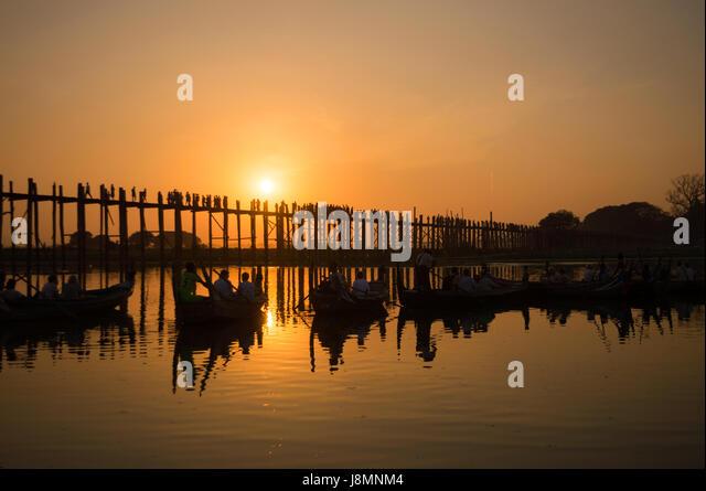 Silhouettes of tourists in boats admiring U Bein bridge over the Taungthaman Lake at sunset, in Amarapura, Mandalay, - Stock-Bilder
