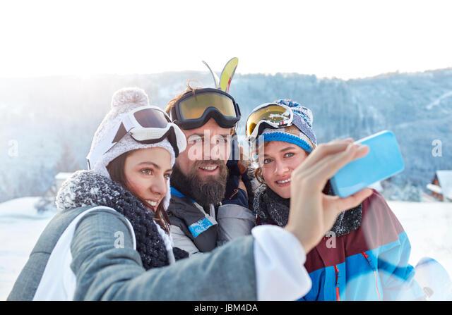 Skier friends taking selfie with camera phone in snowy field - Stock-Bilder
