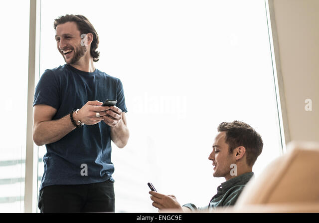 Two men in an office, checking their smart phones. One looking away laughing. - Stock Image