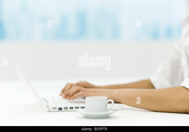 Woman using laptop computer, coffee cup nearby, cropped view - Stock Image