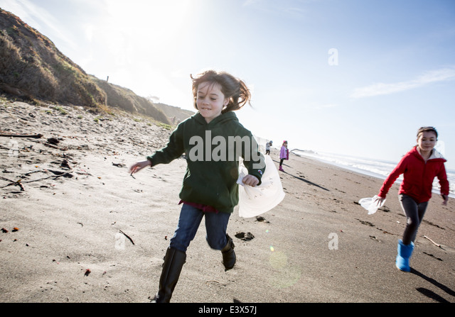 Girls picking up trash on beach cleanup day. - Stock Image